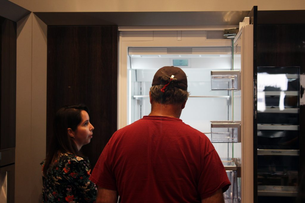 Authorized Thermador representative is showing off a built-in refrigerator hidden in this glossy-wood veneer cabinet.